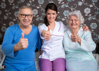 two elderly people with caregiver smiling